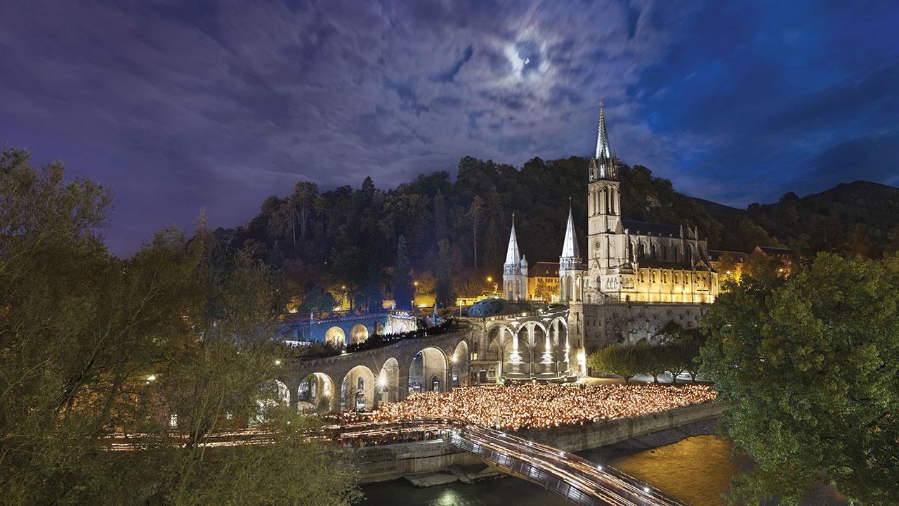 La cathédrale de Lourdes de nuit durant un procession mariale aux flambeaux